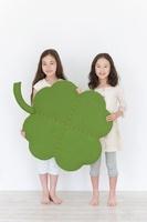 大きな四葉のクローバーのクラフトを持つ2人の女の子