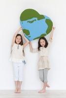 ハート型の地球のクラフトを持つ2人の女の子