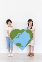 ハート型の地球のクラフトを持つ男の子と女の子