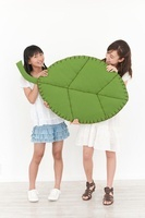大きな葉のクラフトを持つ2人の少女