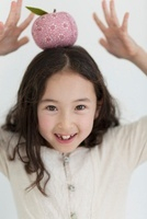 リンゴのクラフトを頭にのせる女の子