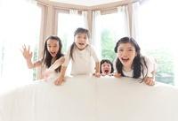 ソファの背もたれの後ろで大声を出す4人の女の子