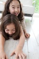ソファの周りでふざける2人の女の子