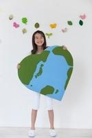 ハート型の地球のクラフトを持つ女の子