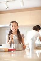キッチンで料理の手伝いをする笑顔の女の子