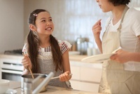キッチンで料理の手伝いをしながら母親と話す娘