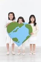 ハート型の地球のクラフトを持つ3人の女の子