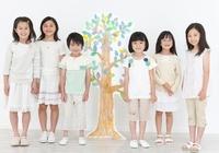 木のイラストの前に並び立つ男の子と女の子