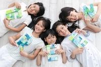 GREENと描かれたクラフトを持って床に寝そべる5人の女の子