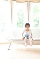 ソファに腰掛ける笑顔の男の子