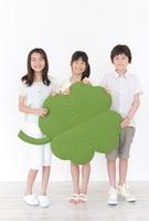 大きな四葉のクローバーのクラフトを持つ男の子と2人の女の子