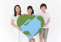 ハート型の地球のクラフトを持つ男の子と2人の女の子