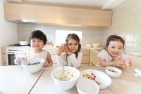 キッチンでおやつを持つ3人の女の子