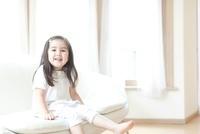 ソファに腰掛ける笑顔の女の子