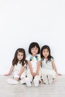 壁に寄りかかって座る3人の女の子