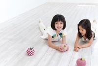 床に寝転んでリンゴのクラフトで遊ぶ女の子2人