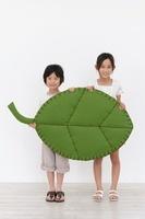 大きな葉のクラフトを持つ男の子と女の子