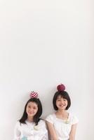 リンゴのクラフトを頭にのせる2人の女の子