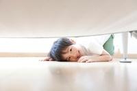 ソファの下をのぞき見る男の子