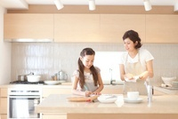 キッチンでメモを取る娘と母親