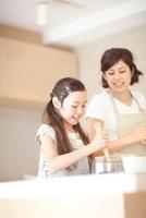 料理の手伝いをする娘