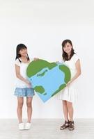 ハート型の地球のクラフトを持つ2人の少女