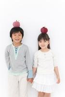 リンゴのクラフトを頭にのせた男の子と女の子