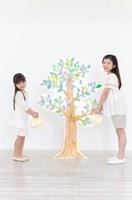 木のイラストに水をやる様子の女の子2人