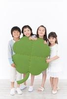 大きな四葉のクローバーのクラフトを持つ女の子と男の子