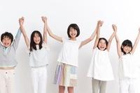 つないだ手を高く上げる女の子4人と男の子