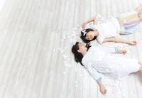 花びらに囲まれて床に寝そべる2人の女の子