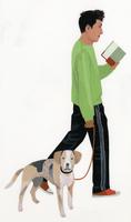 本を読みながら犬の散歩をする男性