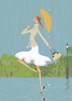 梅雨の雨の中公園で傘を持ちながらスキップする女性