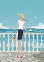 夏のギリシャの海辺で海を眺める女性
