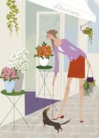 春の花屋の前で犬の散歩をしながら花を愛でる女性
