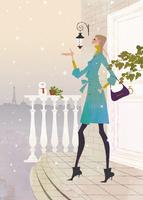 冬のアパルトマンの玄関前で立っている女性