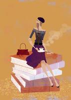大きな本の上に座り、コーヒーを楽しむ女性