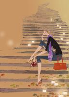 石段に座り本を片手に座る女性