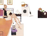 ベッドルームのベッドに座り本を読む女性