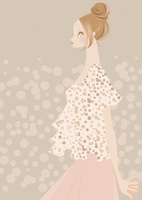 ピンクベージュの水玉柄の服のお団子ヘア女性