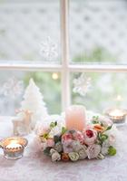 窓辺に飾ったピンクのバラのクリスマスキャンドルリース