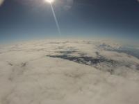 大空から見下ろす北海道の大地 雲海の上の快晴の空に浮かぶ太陽