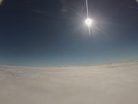曇り空の上は晴天の空 清々しく輝く太陽