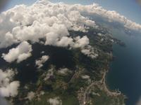 雲の合間から見下ろす町並みと海岸線