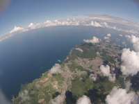 雲の合間から見下ろす町並みと海岸線 広がる日本海