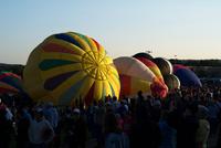 早朝の離陸準備をするホットエアバルーンと観客たち