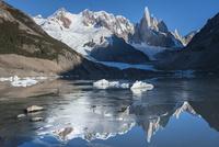 チャルテン付近のトーレ湖に鏡面反射する、パタゴニアのセロトーレ峰と氷河の氷塊