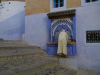 シャウエンの青い街のウドゥ(手洗い場)にいるおじいさんと三毛猫