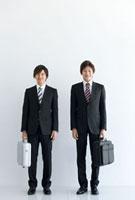 鞄を持って立っているビジネスマン2人