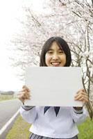 桜の下でメッセージボードを持つ女子中学生